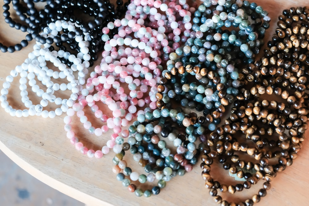 Healing crystal bracelets on top of wooden table