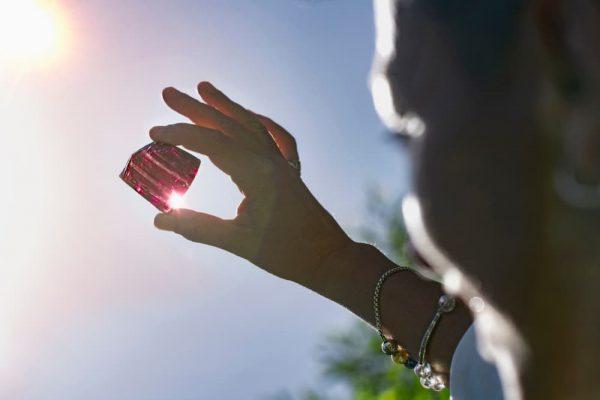 Woman holding purple amethystine quartz crystal in the sun
